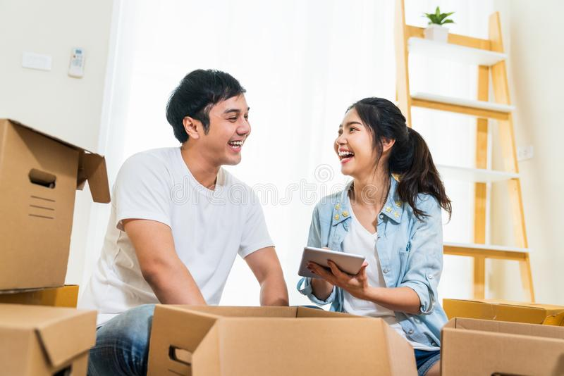 Happy young Asian couple moving in to new house, using digital tablet organizing things and unpacking boxes together royalty free stock image