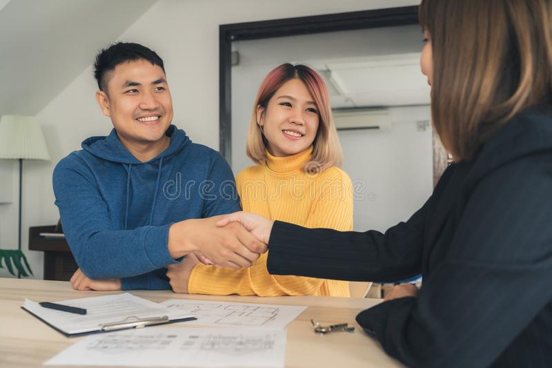 Cheerful young man signing some documents and handshaking with broker while sitting at desk. Happy young Asian couple and realtor agent. Cheerful young man royalty free stock photo