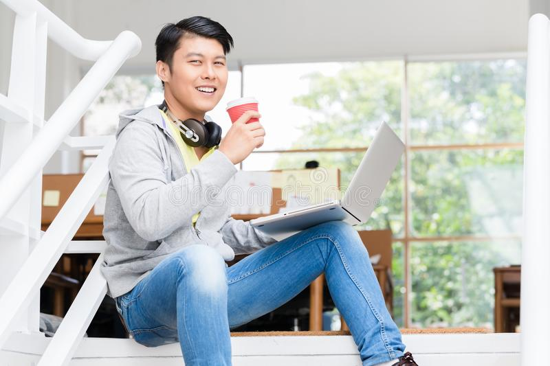 Happy young Asian employee using a laptop in a modern office royalty free stock photos