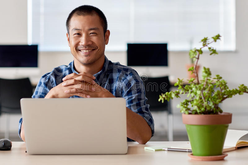 Happy young Asian entrepreneur at work in a modern office stock photos