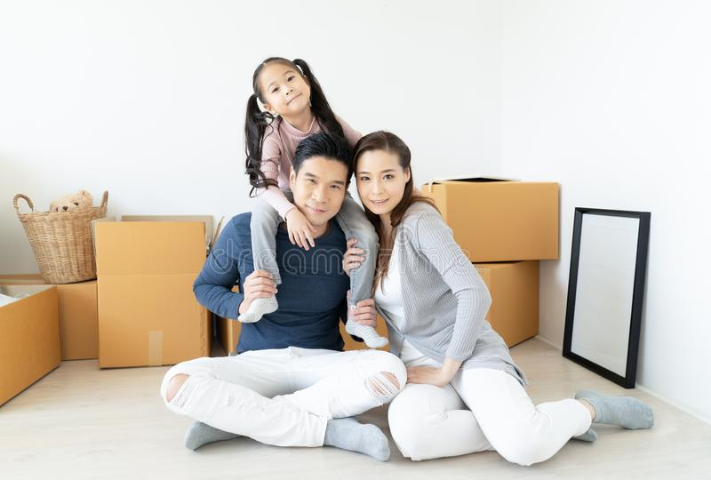 Happy young Asian family moves the boxes to a new home and looking at camera. Moving Concept royalty free stock photos