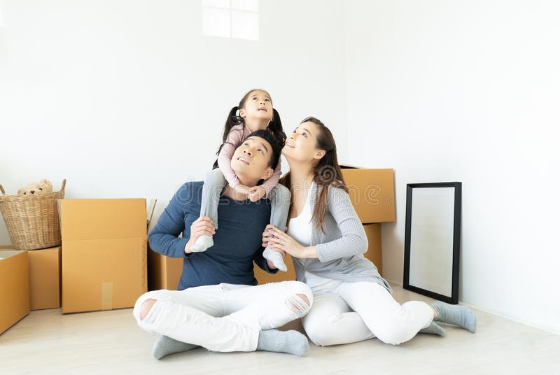 Happy young Asian family sitting on floor in new apartment with moving boxes and looking up into the air with the man carrying stock photography