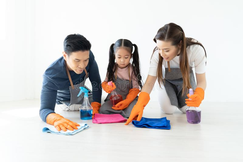 Happy young Asian family of three cleaning their home living room at weekend.Cute little helper. Family housework and household c stock images