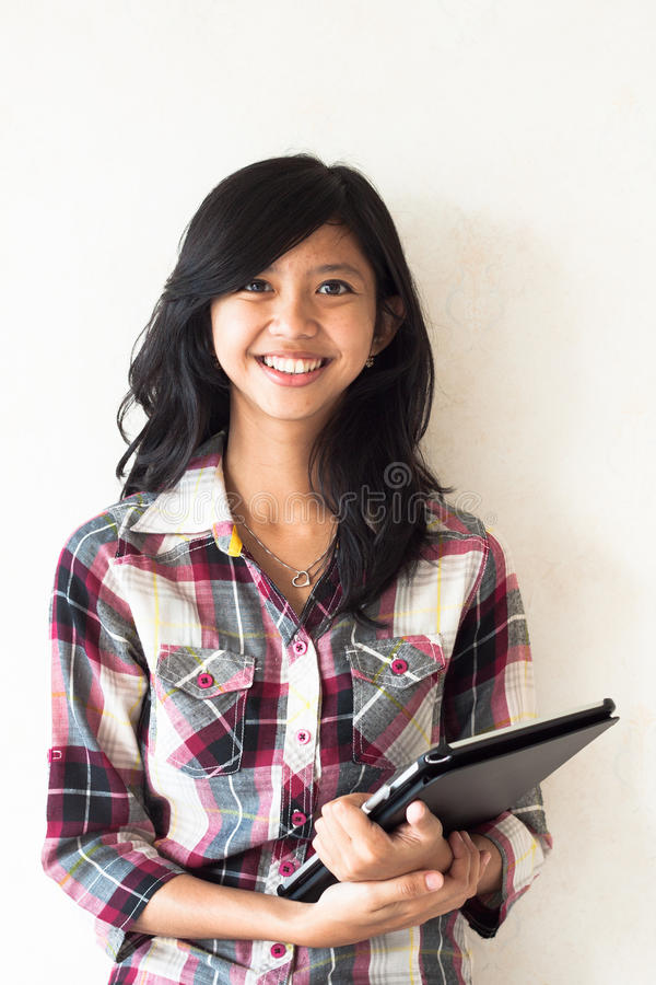 Happy young asian girl holding a tablet pc