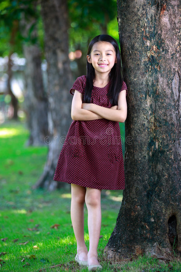 Happy young asian girl standing near a tree stock photo
