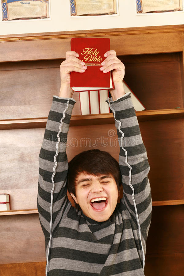 Happy young asian man with bible. Young asian man holding up bible smiling royalty free stock images
