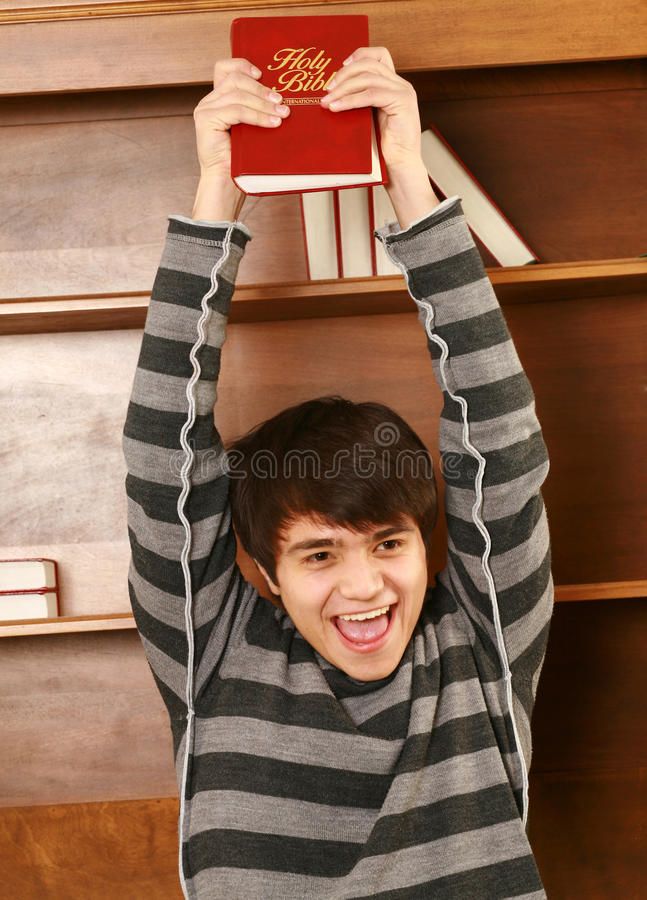 Happy young asian man with bible. Young asian man holding up bible smiling royalty free stock photo