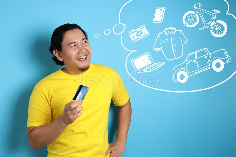 Happy young Asian man smiling and thinking to buy a lot of things while holding a credit card, consumerism concept stock image