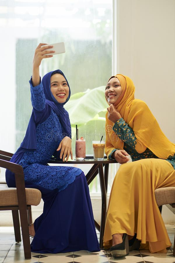 Muslim women photographing in cafe stock photo