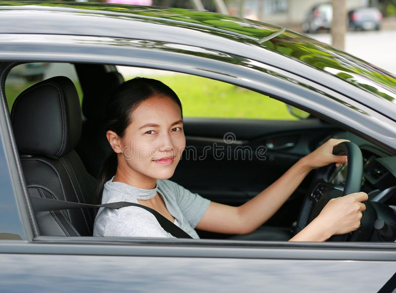 Happy young asian woman in a car while driving stock photos