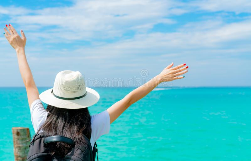 Happy young Asian woman in casual style fashion with straw hat and backpack. Relax and enjoy holiday at tropical paradise beach. royalty free stock image