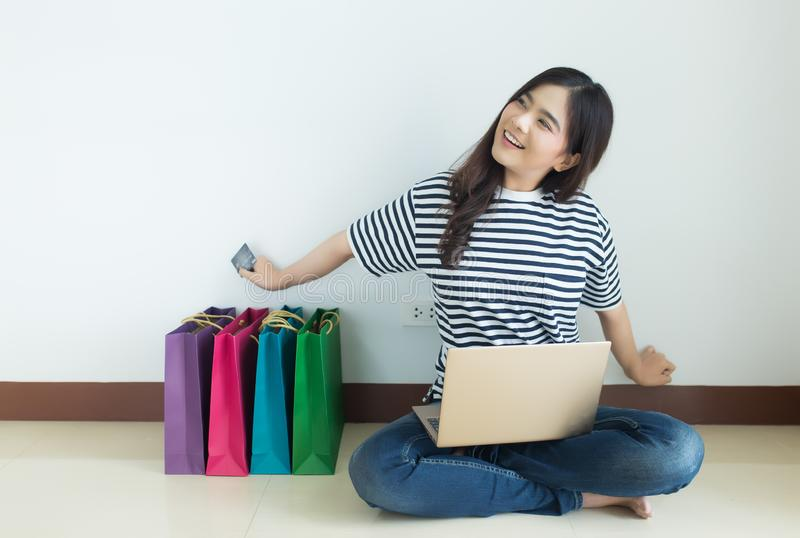 Happy young asian woman holding credit card with her laptop and shopping bags. Online shopping and browsing concept stock photo
