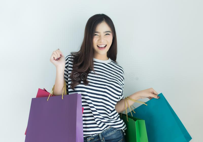 Happy young asian woman holding shopping bags. Online shopping and browsing concept royalty free stock image