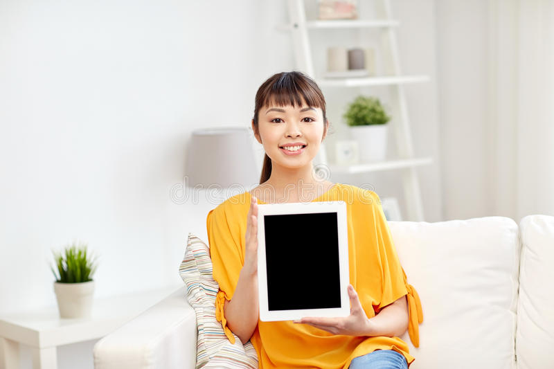 Happy young asian woman with tablet pc at home royalty free stock images