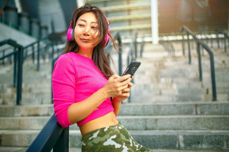 Happy young asian woman training. She is listening to music from earphones and looking at smartphone. Waist up portrait of happy young asian woman training. She royalty free stock image
