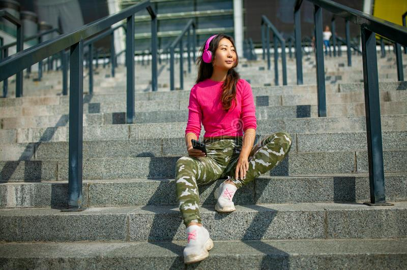 Happy young asian woman training. She is listening to music from earphones and looking at smartphone. Waist up portrait of happy young asian woman training. She stock photo