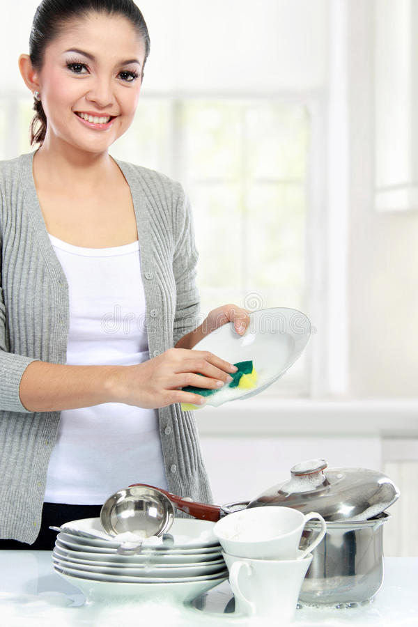 Asian woman washing dishes stock photo
