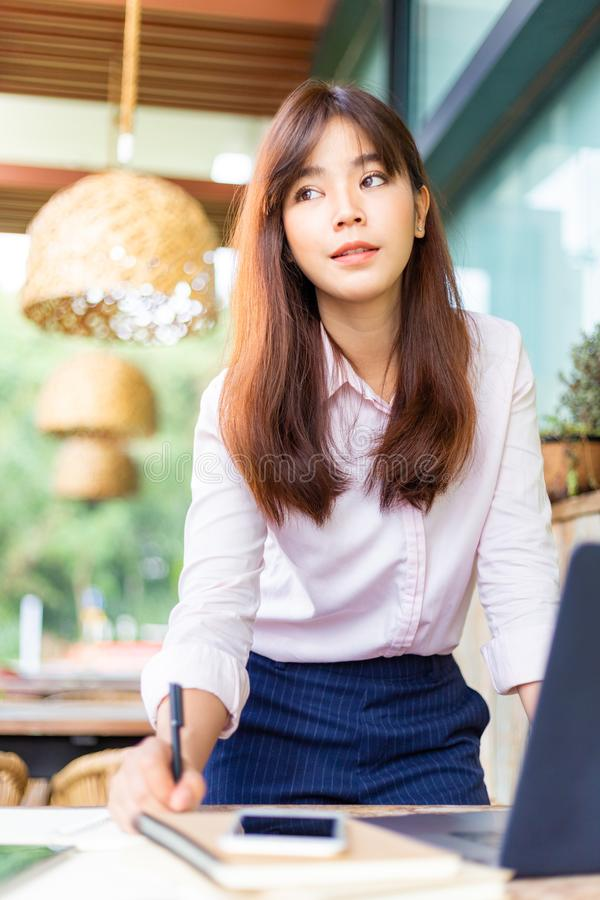 Happy young attractive asian business woman standing while working on her computer at an outdoor patio outside of her office stock image