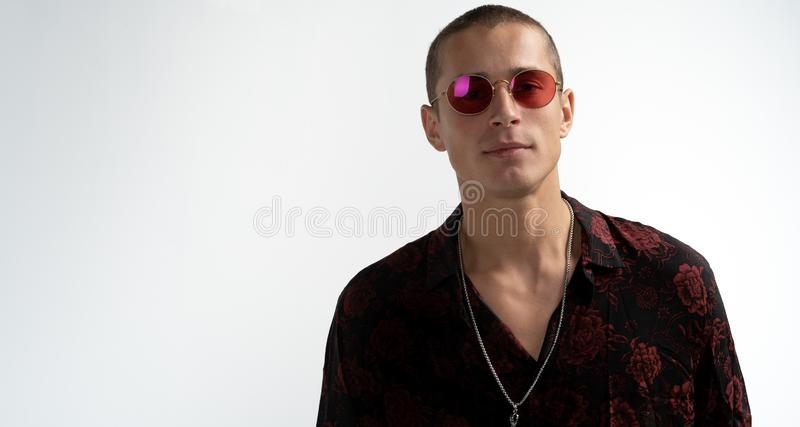 Happy young attractive man with short haircut in red sunglasse, wearing trendy black shirt, looking at the camera royalty free stock photography