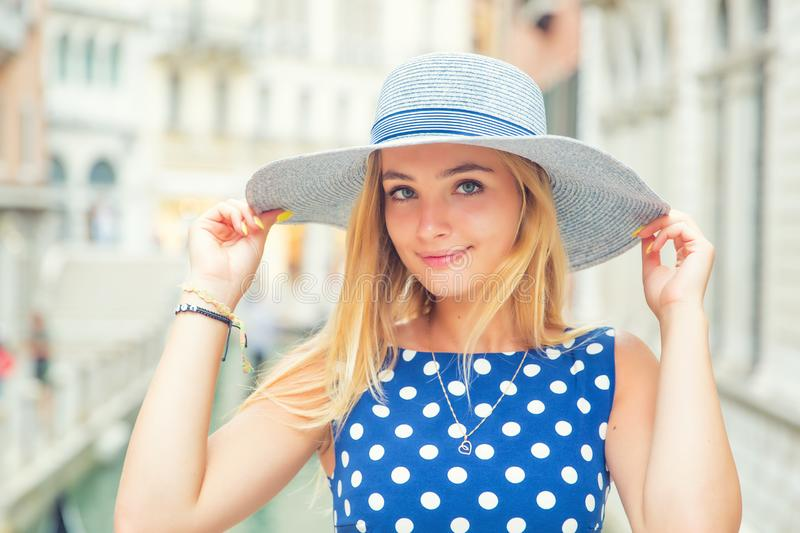 Happy young attractive woman fashion model of venice italy in blue polka dot outfit stock photo