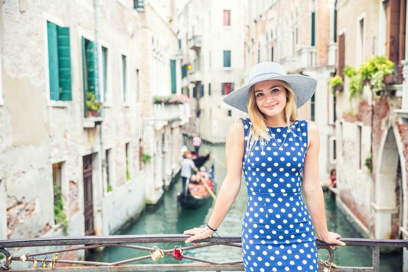Happy young attractive woman fashion model of venice italy in blue polka dot outfit stock photography