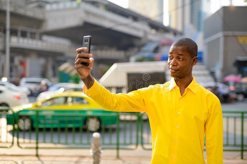 Happy young bald African businessman taking selfie in the city streets outdoors royalty free stock photo
