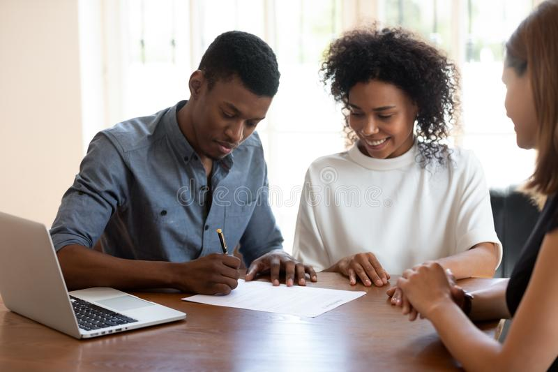 Happy young banking worker watching african ethnicity client signing agreement. Happy young banking worker, real estate agent or financial advisor watching royalty free stock photos