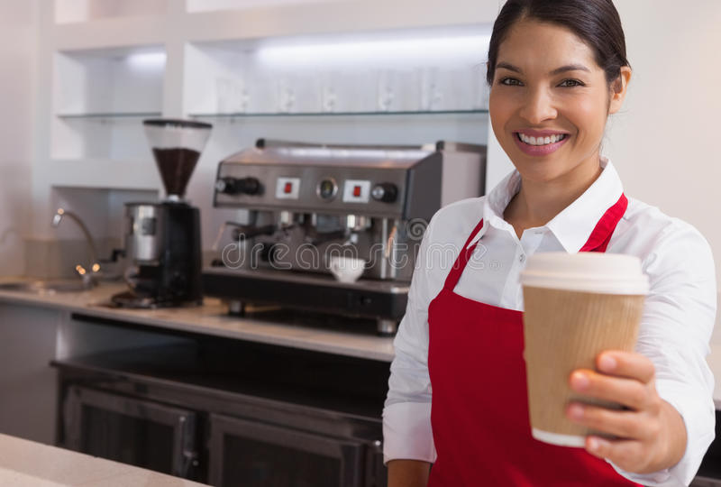 Happy young barista offering cup of coffee to go smiling at camera stock photos