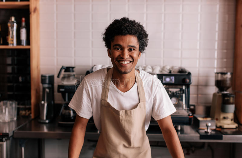 Happy young barista standing at cafe counter stock images