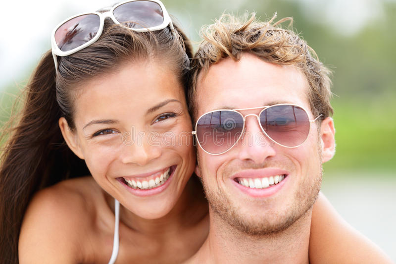 Happy young beach couple closeup portrait. Outdoors in sun. Young people wearing sunglasses eyewear. Joyful interracial couple, Asian woman, Caucasian man stock images