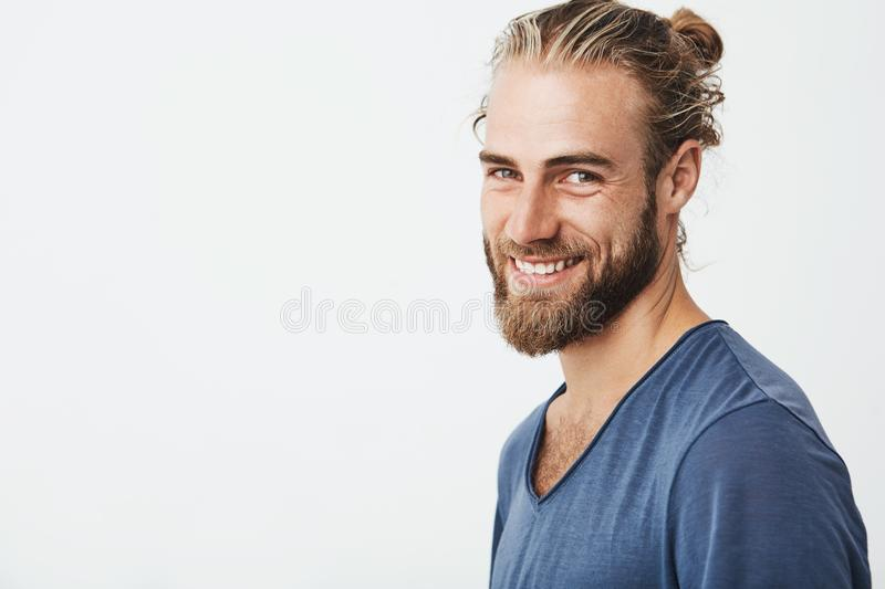 Happy young bearded guy with fashionable hairstyle and beard looking at camera, brightfully smiling with teeth, being stock images