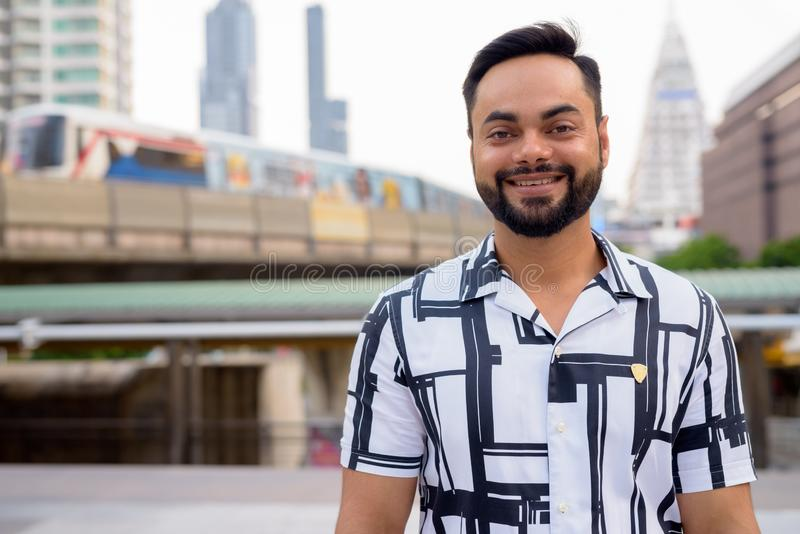 Happy young bearded Indian man smiling against view of train at sky train station stock image