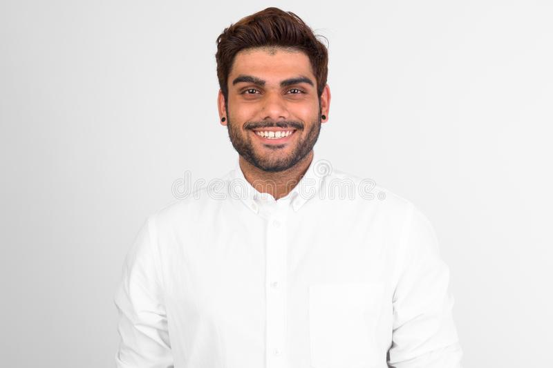 Happy young bearded Indian man smiling against white background royalty free stock photography
