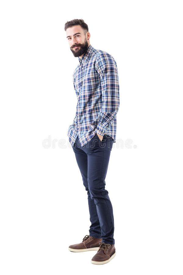 Happy young bearded man in checked shirt with hands in pockets smiling and looking at camera royalty free stock images