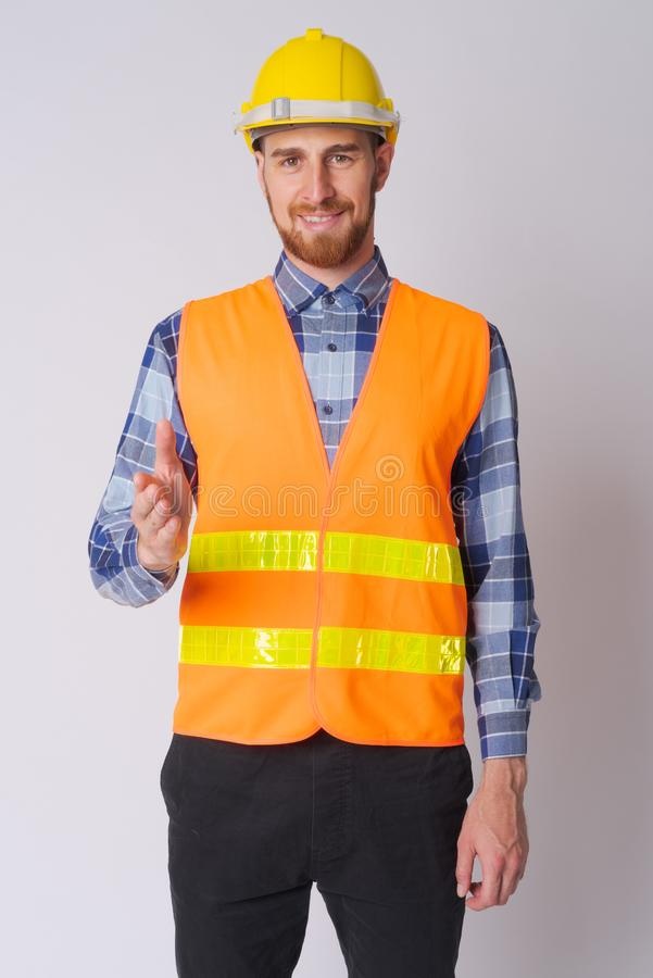 Happy young bearded man construction worker giving handshake stock photography