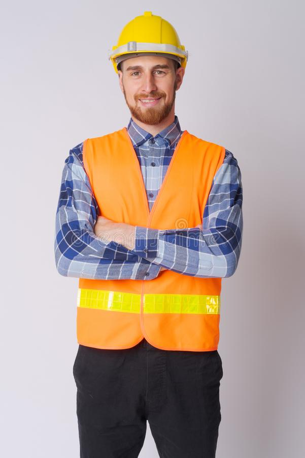 Happy young bearded man construction worker smiling with arms crossed stock photo