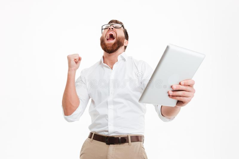 Happy young bearded man using tablet computer make winner gesture. stock photos