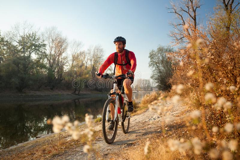 Happy young man enjoying late afternoon mountain bike ride by the river on a clear autumn day royalty free stock photos