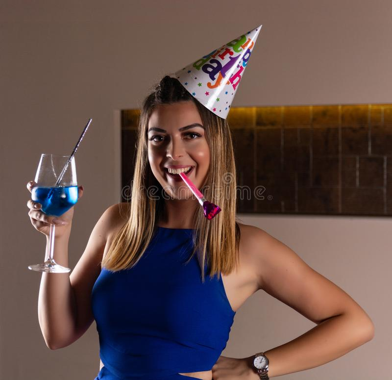 Happy girl with musical blowouts and cocktail blue lagoon in hand and cap on the head celebrates her birthday. Happy young beautiful and attractive girl with royalty free stock photography
