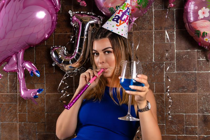 Happy young girl with musical blowouts and cocktail blue lagoon in hand and cap on the head celebrates her birthday. Happy young beautiful and attractive girl stock photos