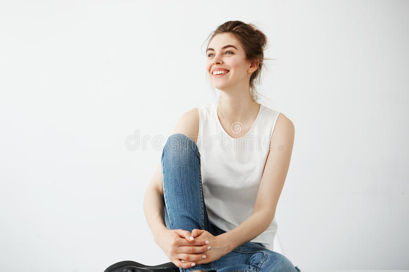 Happy young beautiful brunette girl with bun smiling laughing sitting over white background. Copy space stock image