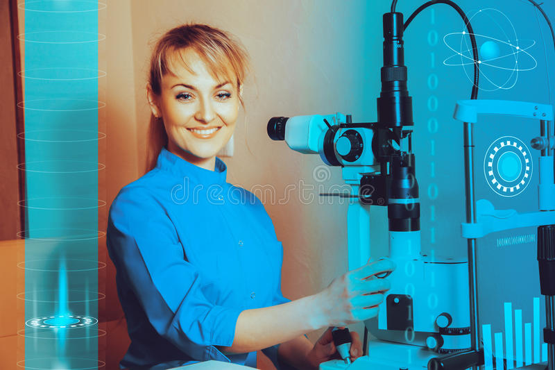 Happy young beautiful Doctor at work machine for checking vision royalty free stock photography
