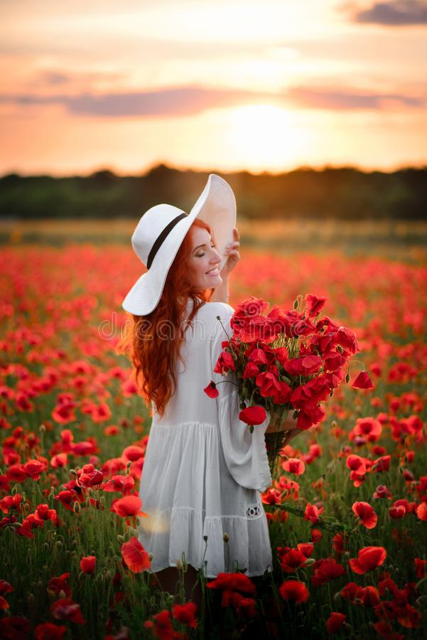 Happy Young beautiful female with bouquet of red poppies stands in flowered field at sunset stock image