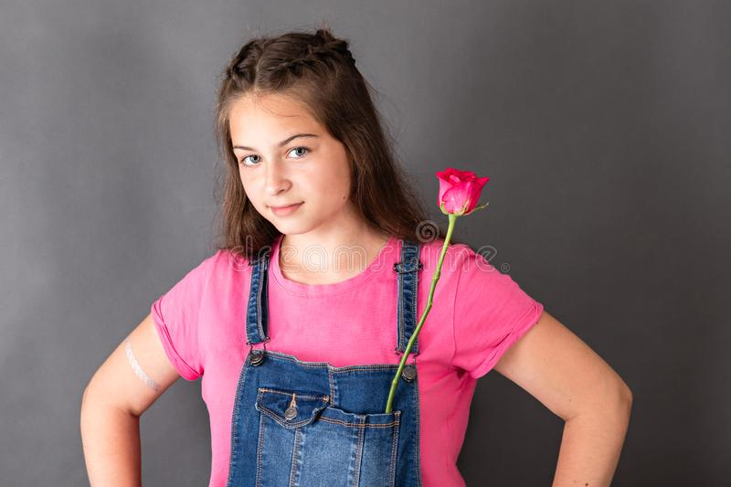 Happy young beautiful girl with rose flower in pocket royalty free stock image