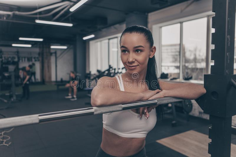 Young sportswoman exercising with barbell at the gym royalty free stock photos