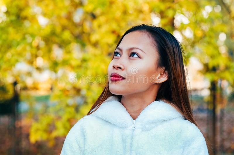 Happy young beautiful woman in autumn park on sunny day, Young woman in white coat during sunset in the park royalty free stock photos