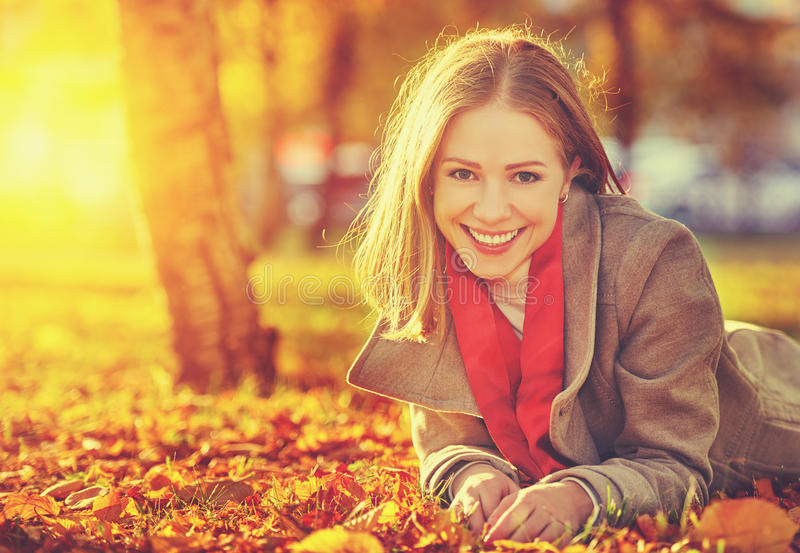 Happy young beautiful woman in the autumn royalty free stock image