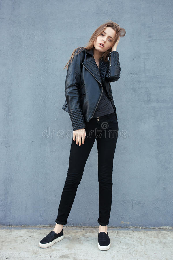 Happy young beautiful woman in black leather jacket black jeans slip-on posing for model tests against textured wall stock photo