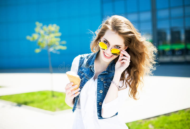 Happy young beautiful woman with curly hair and stylish sunglasses having fun and eating ice cream. Urban style. Outdoor shot. royalty free stock photography