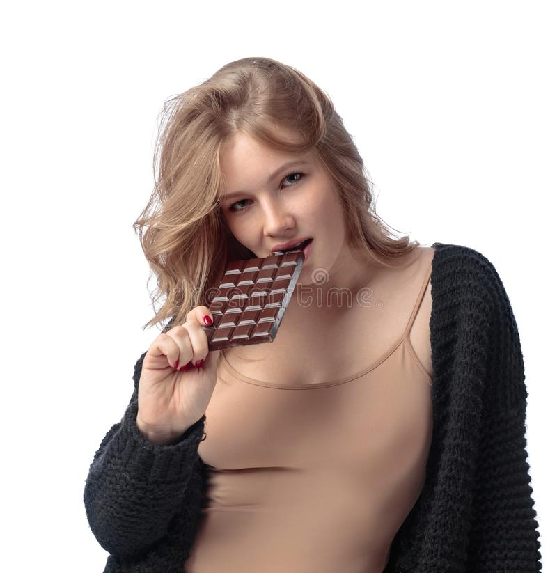 Happy young beautiful woman eating chocolate. royalty free stock photo